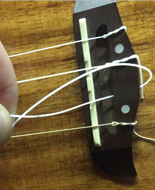 attach new strings to uke saddle